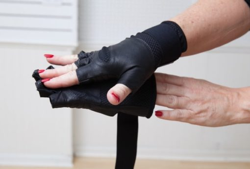 woman putting on WAGs Fusion fitness gloves
